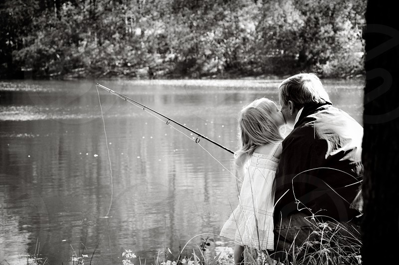 Grandpa and granddaughter fishing. Kiss on cheek. photo