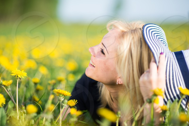Beautiful young woman relaxing in the dandelions flower field photo