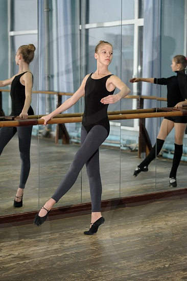 Girls exercising at the barre during ballet class and reflecting in the mirror photo