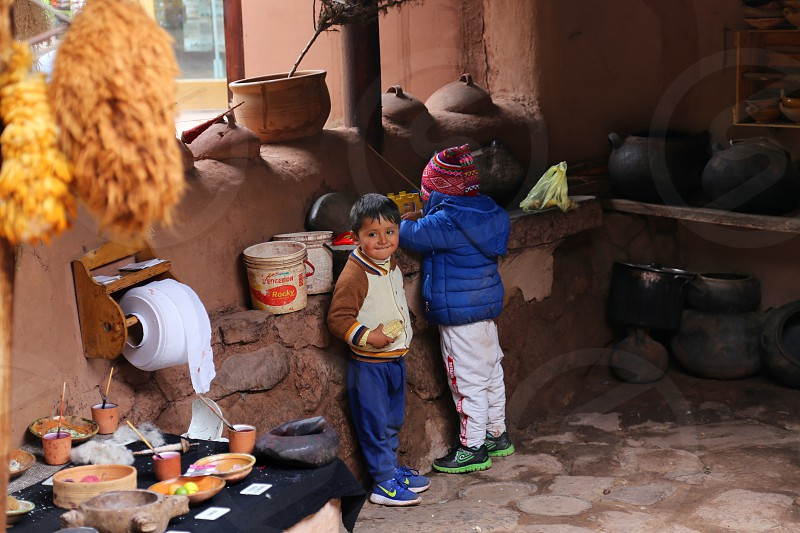 Brothers looking for food in a traditional peruvian kitchen photo