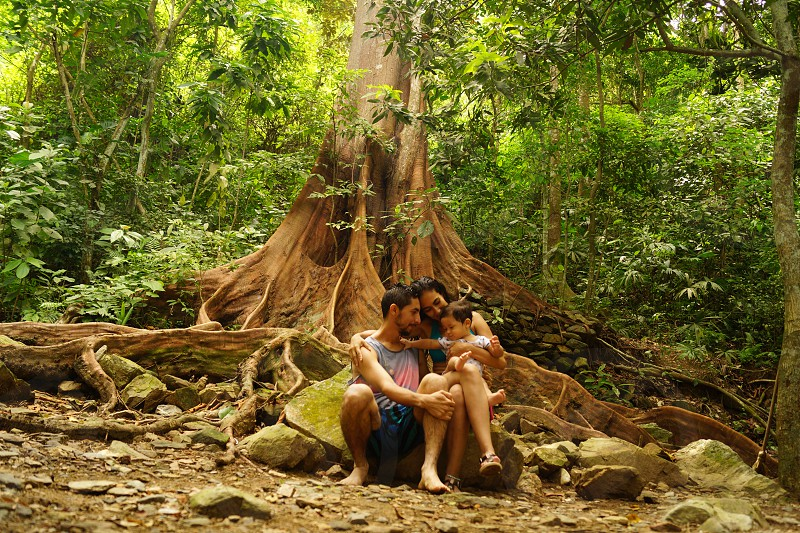 Family hug at the root of a beautiful tree photo