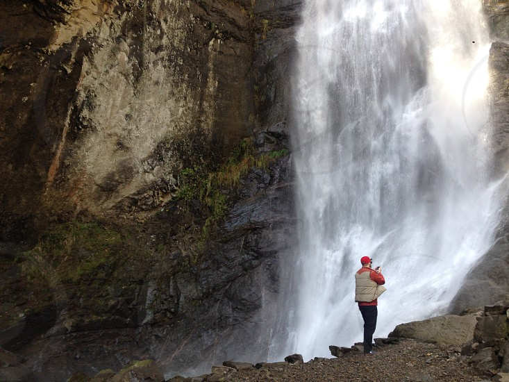 man stands near waterfall during daytime photo