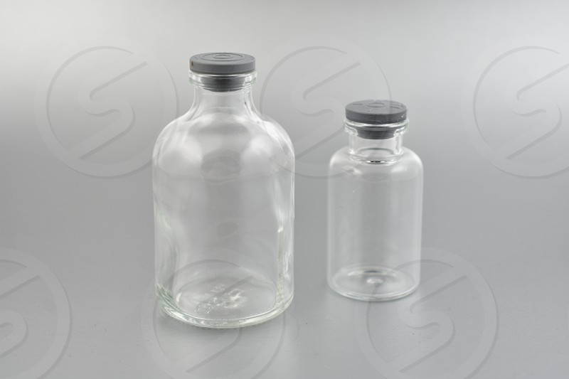 Glass laboratory vials. Glass phial images. Laboratory vial on a silver background. Laboratory vials with a plastic stopper photo