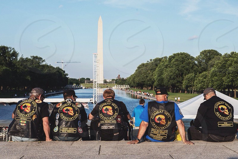 people sitting looking at washington monument photo