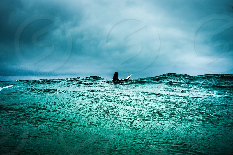 person in body of water under stratus clouds during twilight photo