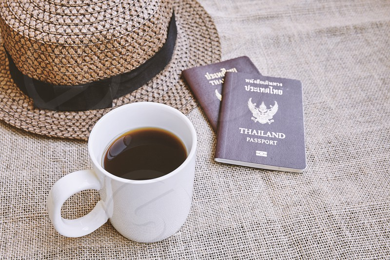 Travel concept Dark brown weave hat with Thai citizen passport and a white cup of black coffee on sackcloth background with copy space or empty space for text photo