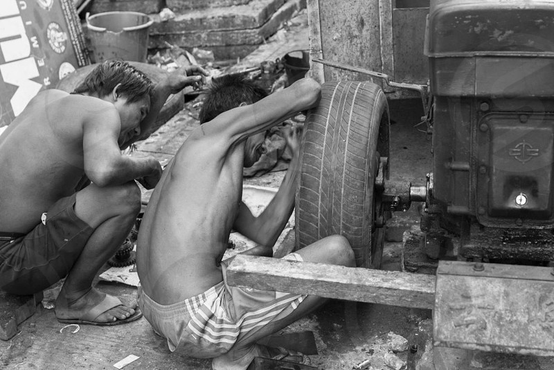 Cooperation. Guys working together fixing an old motor car on the streets of Yangon Myanmar. photo