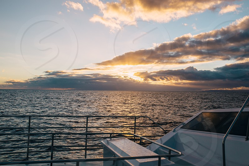grey steel hand railings of a boat on rippling ocean water during sunset photo