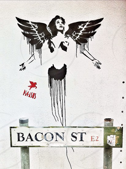 Stencil graffiti in front of a street sign on Bacon Street London England. The graffiti depict singer Whitney Houston with angel wings and is by street artist Pegasus.  photo