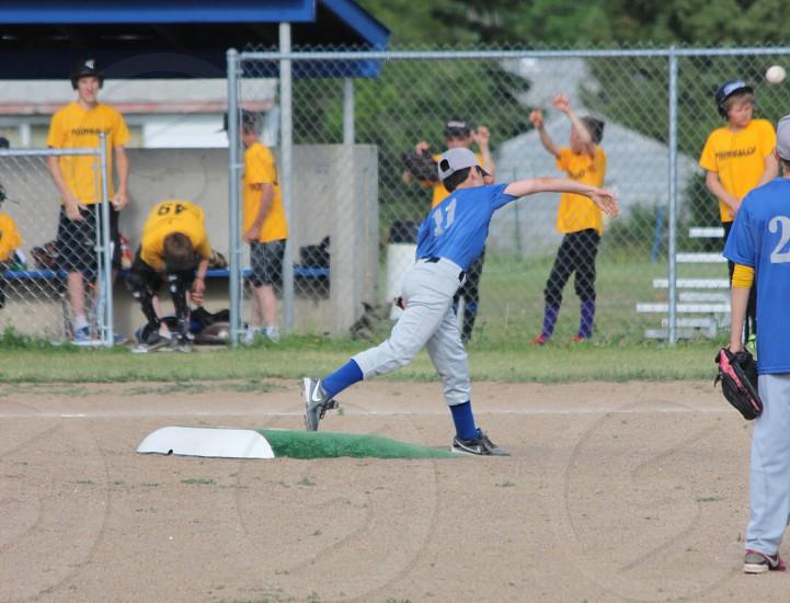 boy in baseball jersey pitching baseball photo