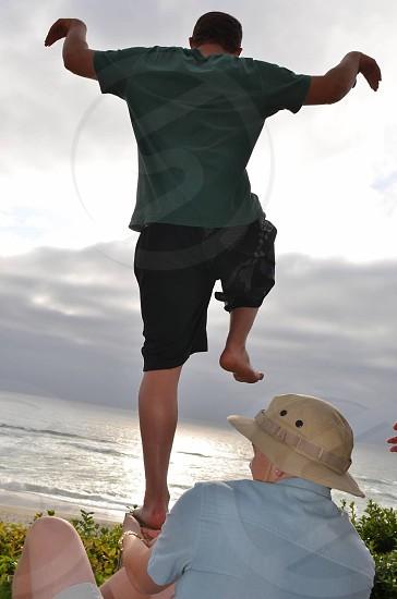 Young man balancing on one foot karate kid kick photo