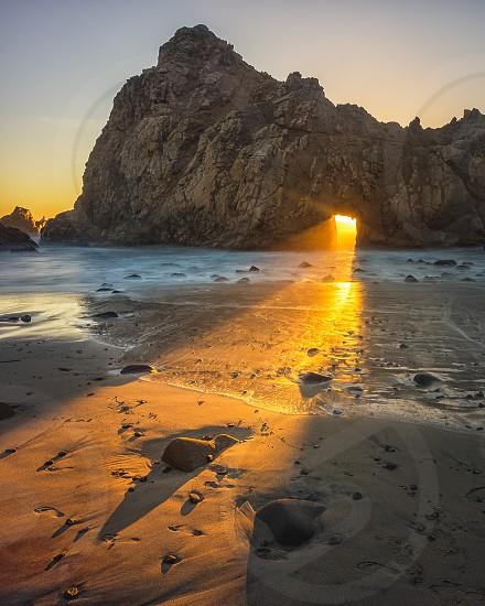 Intense light pours through a coastal keyhole at sunset in Big Sur California. photo