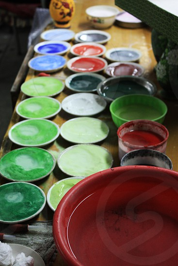 Small paint bowls of many colors on an old table. Green red blue yellow. Location is China. photo
