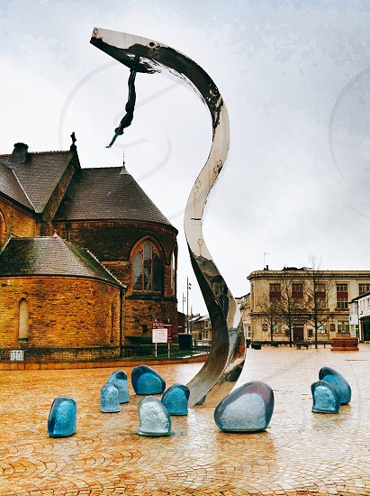grey wave glass sculpture near brown and black concrete house under white sky photo