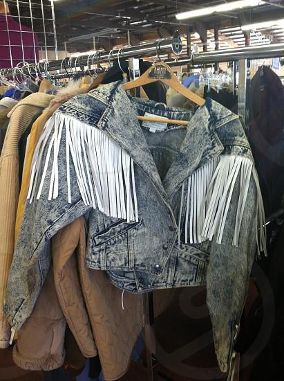 white blue denim fringe jacket on brown clothes hanger on grey clothes hanger rack photo