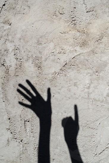 hands shadow on grey wall photo