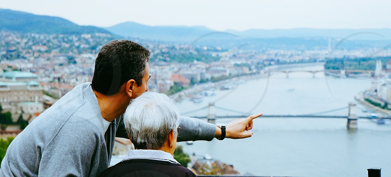 conversation generation view panorama point finger show city elderly photo