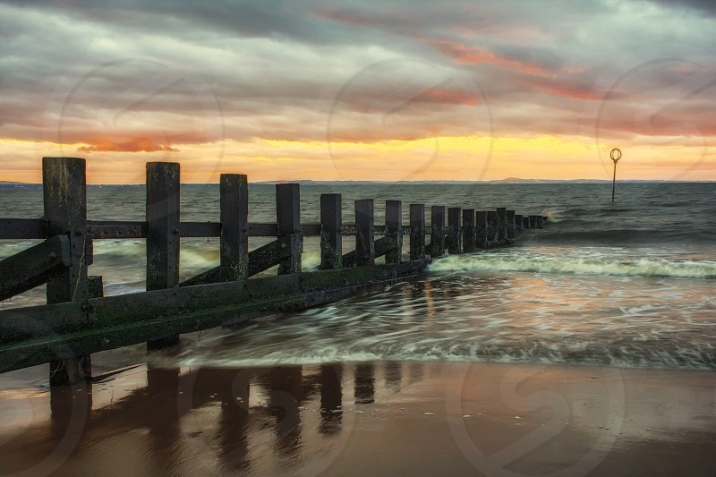 Portobello Scotland at sunset.  Beach seaside surf sunset groin clouds golden hour photo