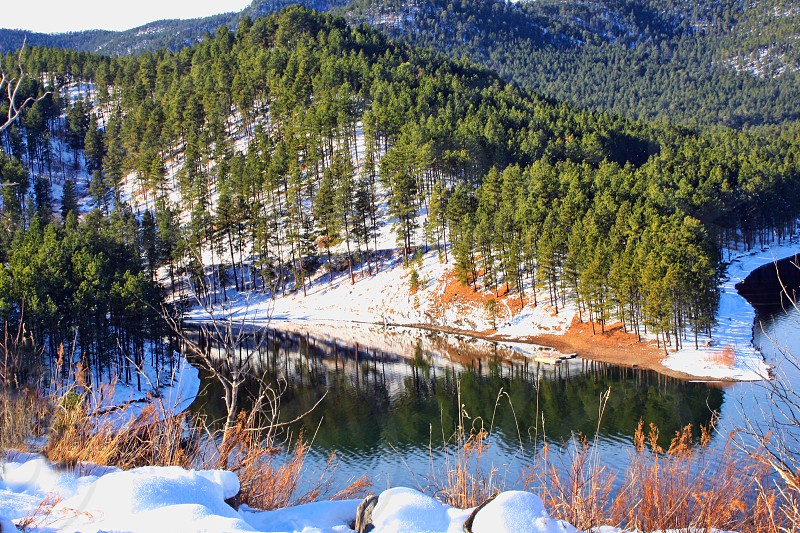 Looking down at a mountain lake in the snow surrounded by pine trees. photo