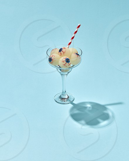 Halloween cocktail with human eyeballs and plastic straw in a glass on a light blue background with hard shadows copy space. photo