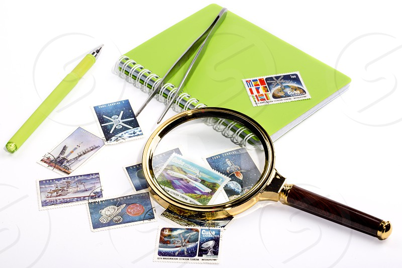 Collection of postage stamps with a magnifying glass and a notebook with a pen. photo