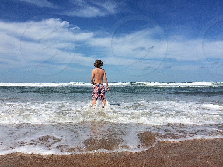 man in pink blue and white aztec printed board shorts standing in front of the sea photo