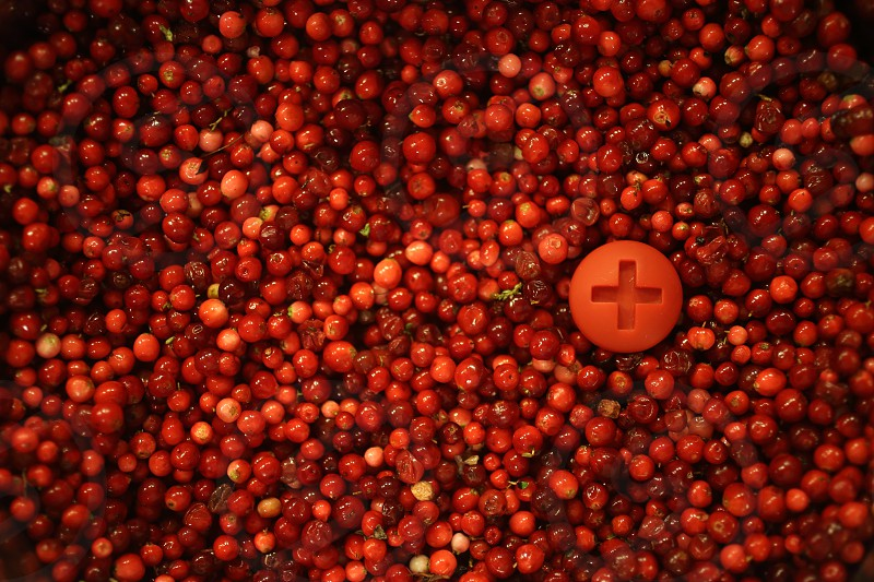 Red background of cranberries with plus sign photo