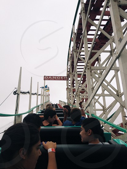 people riding roller coaster ride photo