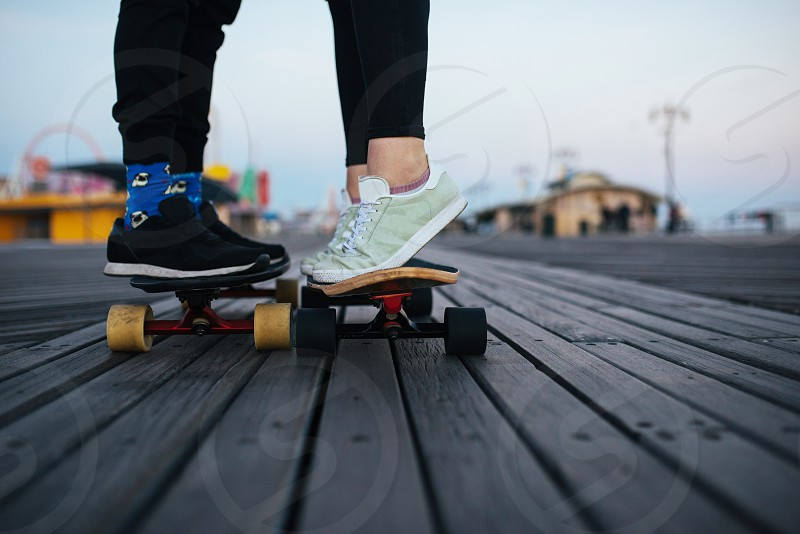 Teenage couple riding long boards on the boardwalk photo