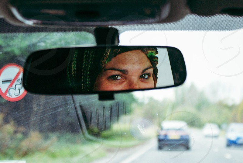woman reflection on car rear view mirror photo