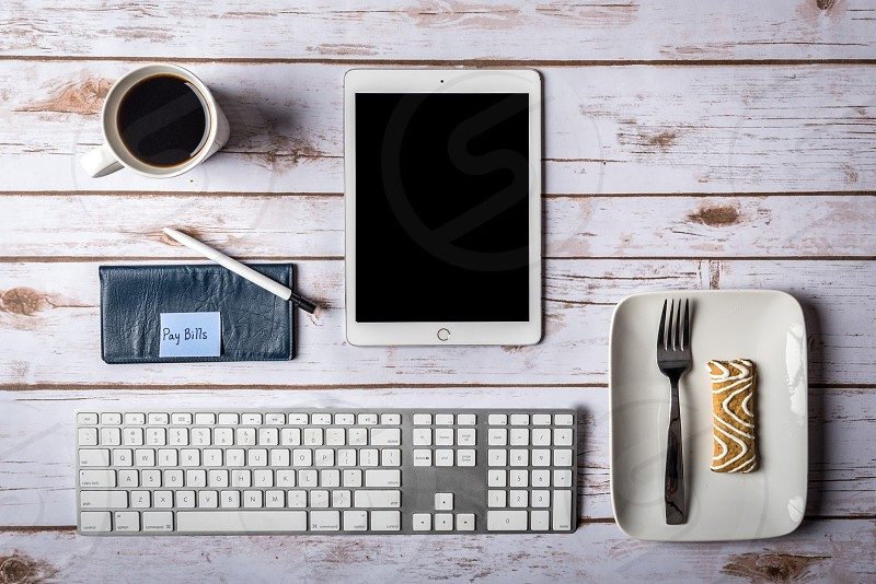 Flat lay with keyboard tablet pc plate with fork and pastry checkbook with pen and pay bills note and cup of coffee on wooden background. photo