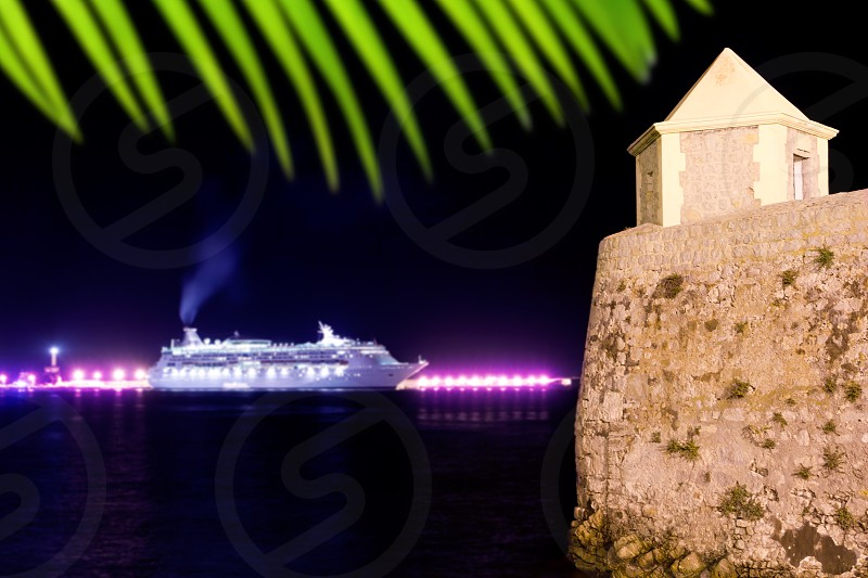 Ibiza night town with cruise ship lights and fort watch tower photo