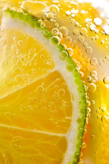 Macro photo of yellow lemon slices and lime with lots of bubbles in a glass with water. Summer refreshing cocktail photo