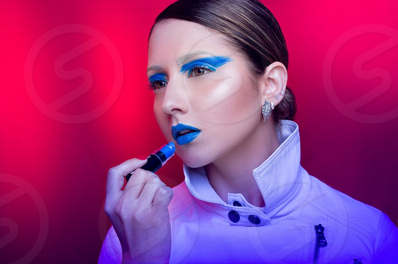 woman in white coat putting blue lipstick on photo