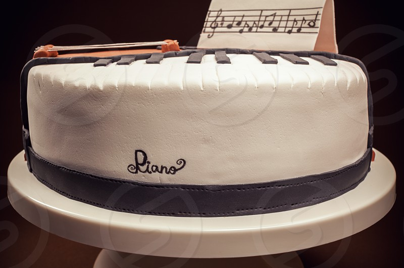Birthday cake decorated with fondant rounded symbolically presenting piano and cello instruments.  photo