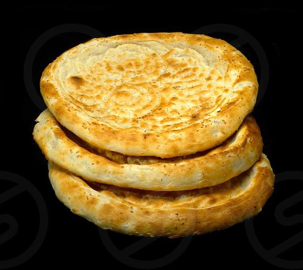 original fresh uzbek bread isolated over black background photo