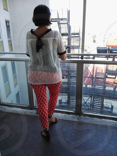 woman in white and black sheer spaghetti back knotted top and red and white pants facing back at the terrace photo