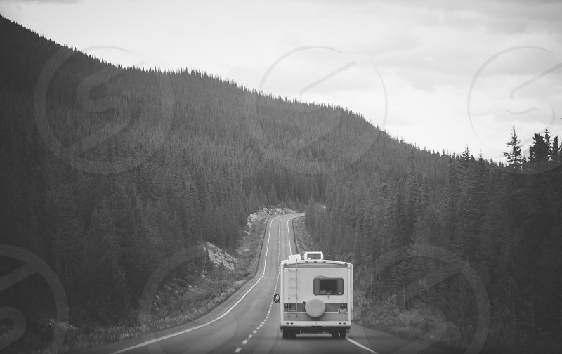grayscale photography of recreational vehicle on road photo