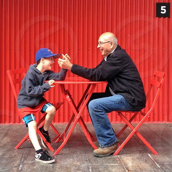Elderly man and boy arm wrestling at bistro seats and table photo