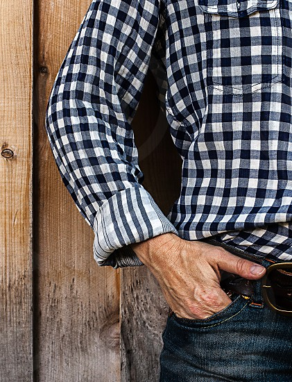 Close-up of anonymous woman's hand tucked into her jeans pocket.  Plaid western shirt and denim jeans. photo
