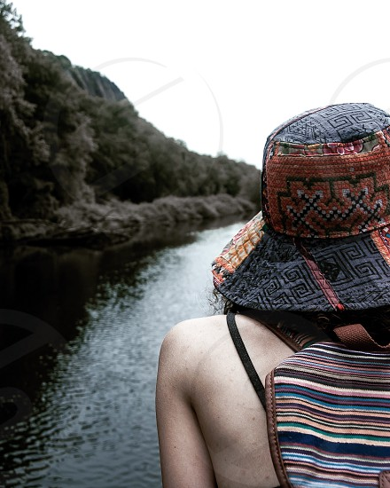female in brown and grey summer hat and brown and blue stripe backpack staring on lake in middle of mountain during daytime photo