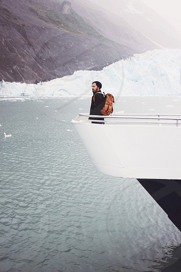 man standing at the front of a boat floating in the ocean next to a snowy bank photo