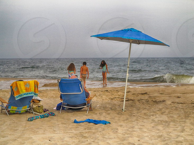 2 person sitting on blue lounger beside blue umbrella on seashore near 3 children photo