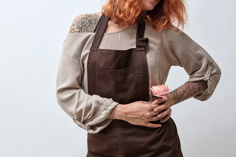 A woman with red hair in a brown apron holds in her hand a pink flower of the Ranunculus on a gray background. Mother's Day photo
