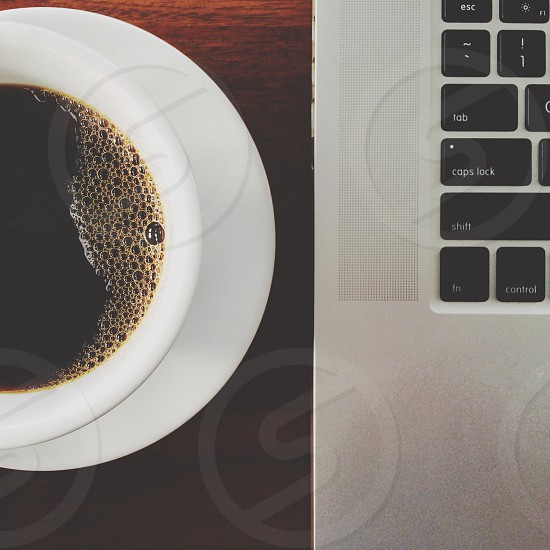 white cup of coffee beside a macbook laptop photo