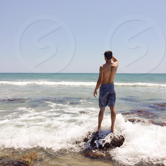 man in blue shorts standing on top of rock near body of water photo
