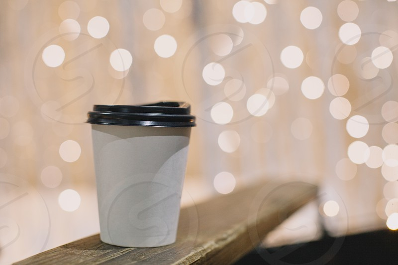 white cup with black cover background yellow lights photo