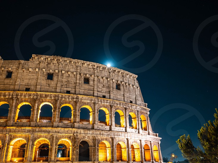 Roman colosseo by night. Ancient colosseum on black sky background. photo