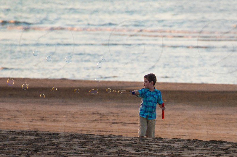 boy blowing bubbles on a beach photo