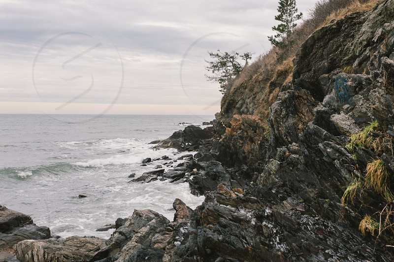 body of water with raging waves near the rocks and the edge of the cliff under grey and white clouds during day time photo
